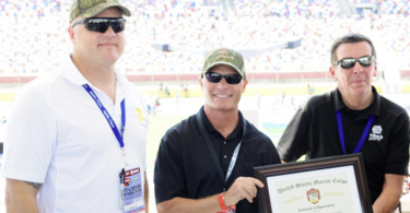 Gunnery Sergeant Eric Dueweke presents Keith Wilson, Affinia CEO and Paul Kortman, brand manager NAPA Filters a certificate of appreciation for NAPA Filters' support of the Intrepid Fallen Heroes Fund.