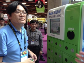 Alex Lee of Kentfa Advanced Technology Corp., demonstrates the company's battery dispenser that allows users to retrieve fully charged vehicle batteries while exchanged an exhausted battery, much like propane gas dispensers in the United States.