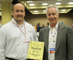 "general cable's ryan kiefer (left), regional sales manager automotive products, accepts the exemplary service award for a new vendor from apa vice chairman robert ""bob"" duxler (right) of automotive inventory management systems."